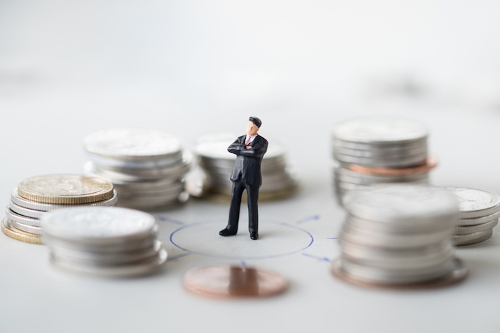 small toy figure of a man wearing a suit surrounded by various coins in varying amounts